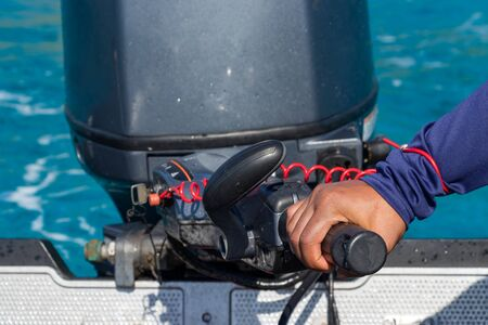 Male hand driving a inflatable boat holding the tiller of an outboard motorboat, close up, outdoors.