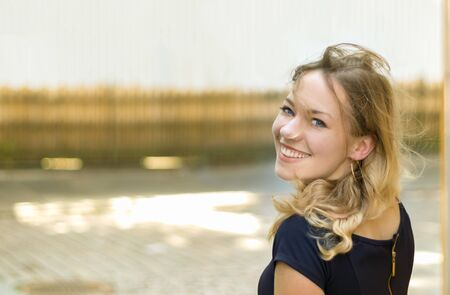 Portrait of a blonde young woman with blue eyes. toothy smile looking at camera, cheerful, over an urban background, outdoors.