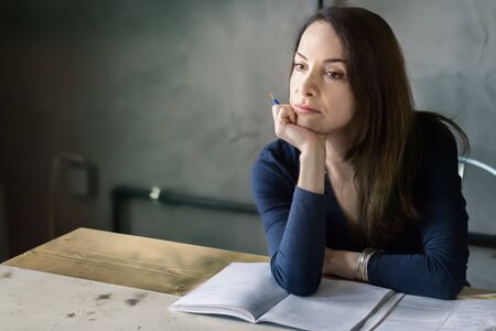 Adult woman sitting alone on a table, thinking, concerned, holding a pen with her hand on her chin.
