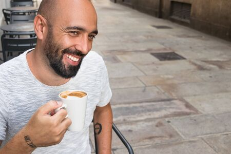 Portrait of a spanish man with beard having coffee sitting outdoors, smiling, happy, looking away, enjoyment.