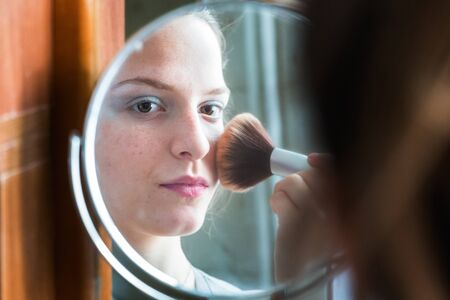 Teenager girl applying powder with a brush looking her reflection on a round mirror at home