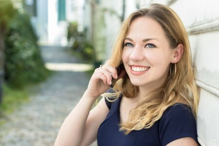Portrait of an austrian young woman blonde with blue eyes speaking on a phone outdoors, smiling.