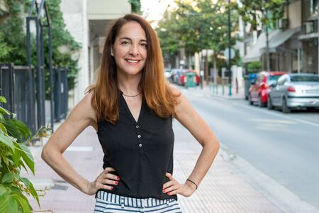 Portrait of a mature woman, 40s, smiling looking camera with her hands on her hips outdoors in a city.