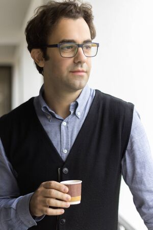 Portrait of a man holding a paper cup of coffee, wearing eyeglasses, thinking, profile view.