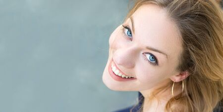 Portrait of an austrian young woman blonde with blue eyes looking up, toothy smile, healthy teeth. 免版税图像 - 150378359
