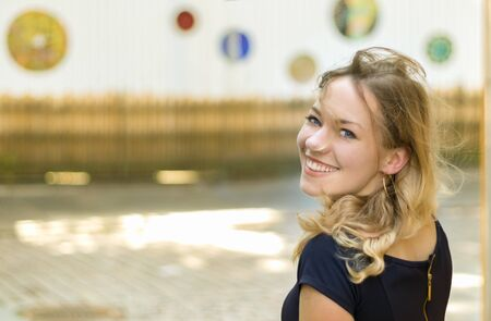 Portrait of an austrian young blonde woman with blue eyes turning her head smiling at camera, cheerful, outdoors.
