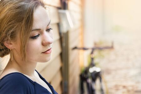 Portrait of blonde woman looking down, pensive, dreaming in a nostalgic way, outdoors. 免版税图像