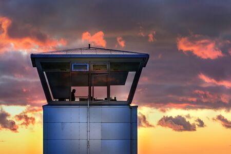 An air traffic control tower with the silhouette of an unidentifiable male traffic controller standing, cloudy weather, Iceland. 스톡 콘텐츠