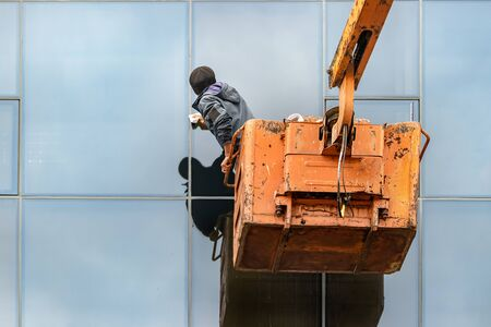 A male unidentifiable worker cleaning the windows of a building standing on a crane, outdoors.