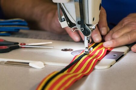 Male hand sewing golden and black strips on a red costume belt in Belfast, Ireland, UK.