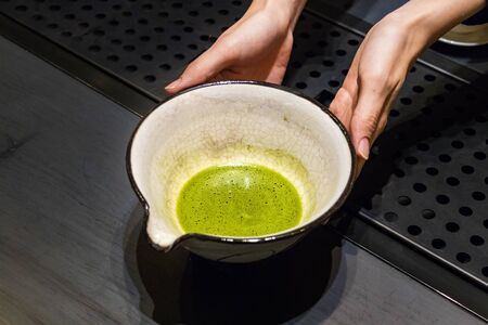 Female barista hands showing a ceramic bowl with matcha tea at a counter in Busan, Korea.