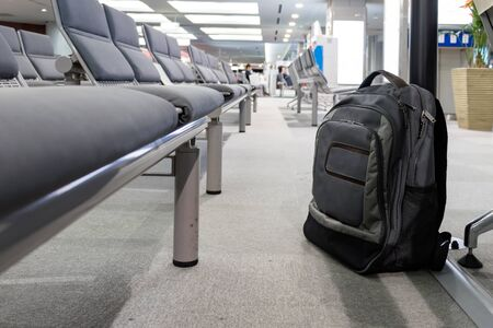 Unattended cabin backpack abandoned on the floor at the boarding waiting hall of an airport.