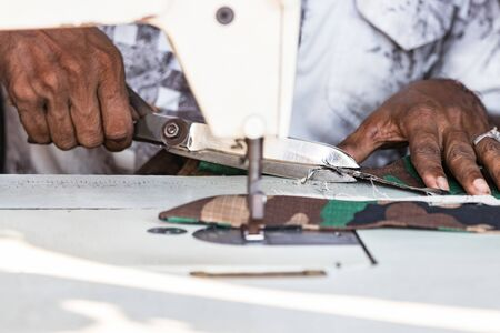 Female hands of a seamstress cutting fabric with a scissors in Galle, Sri Lanka.