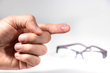 A male finger holding a contact eye lens over a blurred eyeglasses as background.