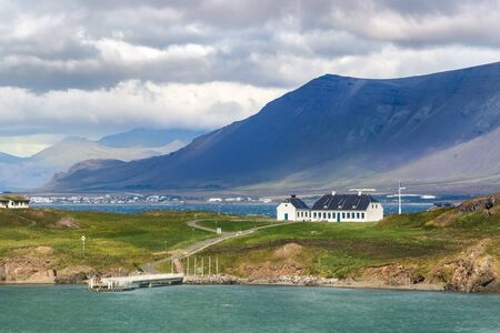 The Videy Island and an old white guest house viewed from the coastline of Reykjavik, Iceland.
