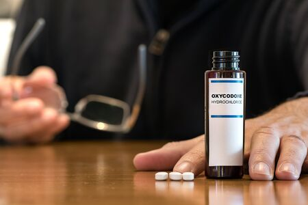 Prescription bottle with Oxycodone tablets on a table with a human hand next ot it.