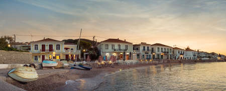 Panoramic view of the coastline, taverns, restaurants and old buildings located on Anargirou street at sunset in Spetses, Greece.