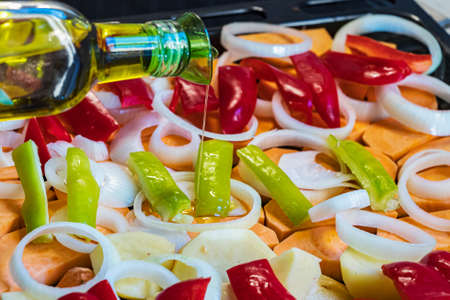 Bottle pouring olive oil on raw chopped vegetables placed on a oven tray.