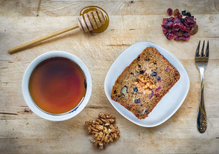 A slice of vegan cake with super fruit and nuts, honey and a cup of tea, hight angle view.