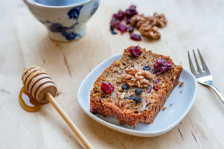 A slice of vegan cake with super fruits, nuts and honey on wooden table.