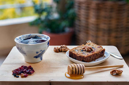 A slice of vegan cake with super fruit and nuts, honey and a cup of tea on wooden table.