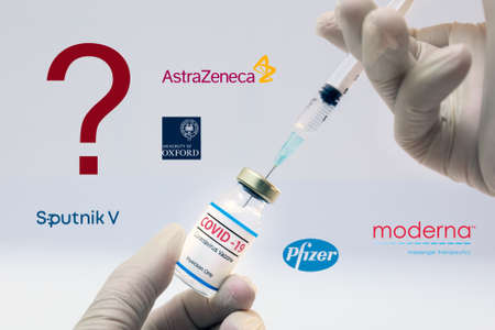 Athens, Greece - Januar06, 2021: Dr. hands holding a bottle of coronavirus vaccine with a question sign and the Pfizer, Sputnik V, Moderna, Astra Zeneca and Oxford University logos.