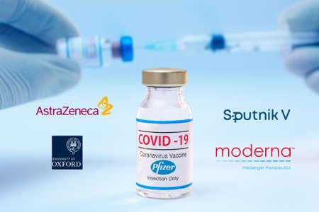 Athens, Greece - Januar06, 2021: Bottle of Pfizer coronavirus vaccine with the Sputnik V, Moderna, Astra Zeneca and Oxford University logos as background.