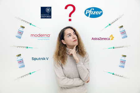 Athens, Greece - Januar06, 2021: A serious woman with questions and doubts with vaccine bottles and the logos of Astra Zeneca, Pfizer, Moderna, Sputnik and Oxford University s background.