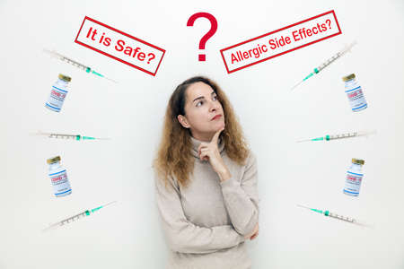 A serious woman with questions and doubts with covid-19 vaccine bottles and It is Safe and Allegic Side Effects signs.