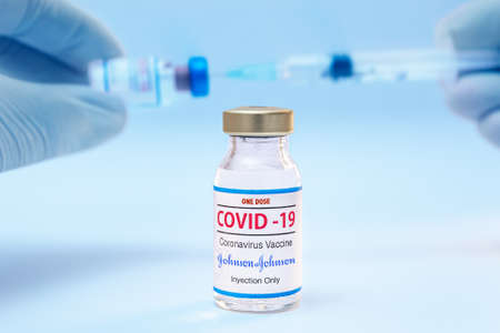 Athens, Greece - January 29. 2021: Bottle of a one dose of coronavirus Johnson and Johnson vaccine and doctor hands with syringe background.