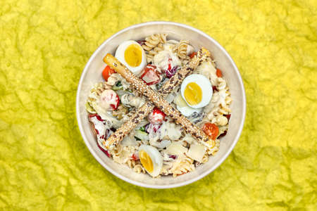 High-angle view of a Mediterranean salad with pasta, eggs, vegetables adn breadsticks.