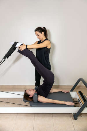 A woman practicing exercises with a pilates personal trainer on reformer. Stock Photo