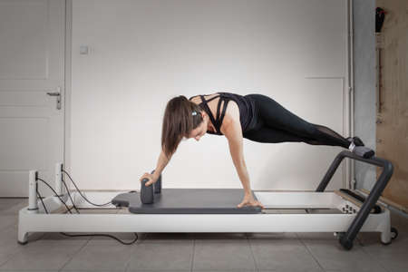 A woman doing pilates exercises with a reformer bed at her private gym.