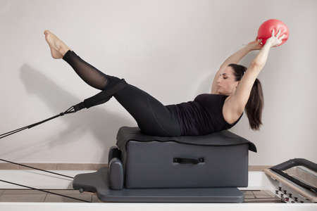 A woman doing pilates exercises pulling elastic bands with her legs and holding a ball with her hands. Standard-Bild