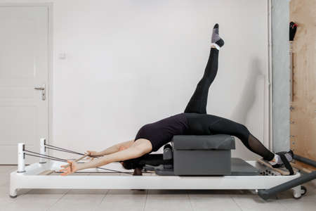 A woman doing pilates exercises with a wooden stick on a reformer bed. Standard-Bild