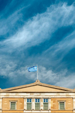 Greek flag on the greek parliament by blue sky.