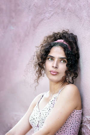 Portrait of a tunisian woman looking away by pink wall, casual clothes, outdoors.