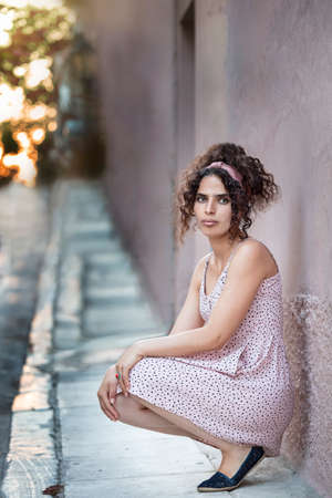 Portrait of a tunisian woman looking camera, crouched down, casual clothes, outdoors.