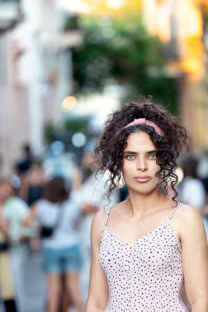 Portrait of a tunisian woman looking camera, casual clothes, outdoors.