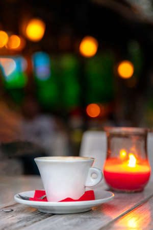 Cup of coffee on a wooden table at night by candle light, outdoors.