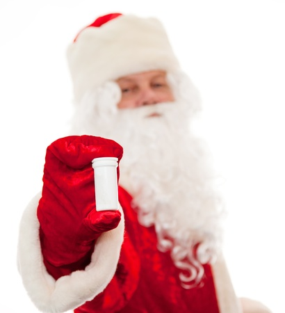 Close up of Santa Claus with a bottle for pills isolated on white. Sharpness on the bottle drive. photo