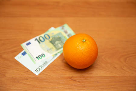The orange and euro. The table is orange. The banknote of 2002 andf 2013. Pay for food, fruit. It contains a lot of vitamin C. The focus is on the orange.