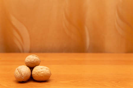 Walnuts on the orange table. Golden background. Walnuts are in the corner