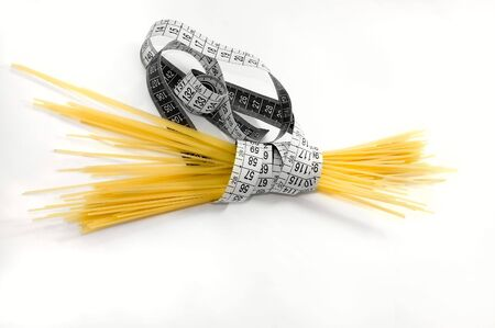 Spaghetti with a centimeter to illustrate weight loss and dieting and vice versa photo