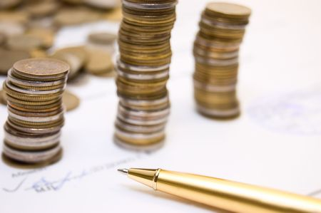 Coins and gold pen on  written contract background  photo