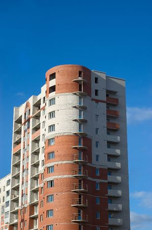 High multistory  of red and white bricks on sky background photo