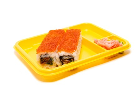Yellow plate with rolls of sushi on white background photo