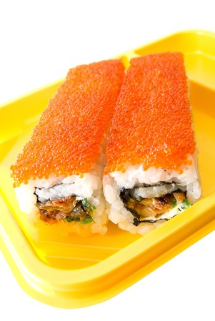 Rolls of sushi at yellow table on white photo