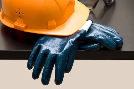 Orange hardhat and  leather gloves on table photo