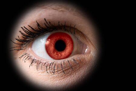 extreme close-up of red bllod female eye on dark photo
